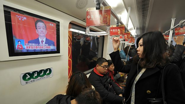 Commuters watch TV in Shanghai